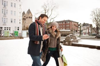 Ein junges Paar auf Shopping-Tour in einer verschneiten Stadt. In den Einkaufstaschen werden unter Umständen erhebliche Mengen an virtuellem Wasser nachhause getragen.