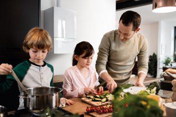 Ein Vater kocht mit seinen beiden Kindern. Die Tochter bereitet das frische Gemüse vor, der Sohn rührt im Kochtopf. Hier trifft viel virtuelles Wasser auf nur geringen realen Wasserverbrauch.