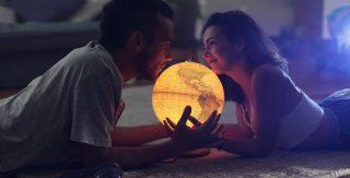 3. Auf dem Boden liegendes Pärchen hält einen leuchtenden Globus. Quelle: unsplash.com