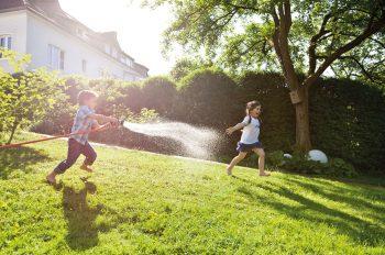 Kinder spielen im Garten. Mit großem Vergnügen spritzen sie sich mit dem Gartenschlauch nass. Hier macht Wasser sparen wirklich keinen Sinn.