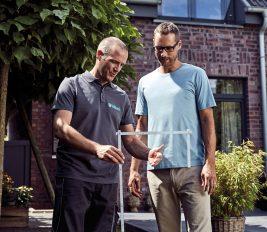 Ein Eigenheimbesitzer bespricht mit seinem Heizungsfachmann, wie eine energiesparende Heizung für das geplante Gewächshaus möglich ist.