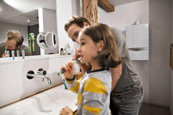 Vater und Tochter putzen sich die Zähne. Sie haben dabei den Wasserhahn abgedreht und sparen deshalb viel Wasser.