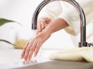Eine Frau lässt aus dem Wasserhahn Wasser sanft über ihre Hand laufen. Trinkwasser ist spürbar lebenswichtig.
