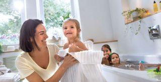 Im Hintergrund planschen zwei Kinder in der Badewanne. Im Vordergrund trocknet eine Mutter ihr Kind ab.