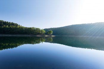 Sonnenstrahlen lassen die Wasseroberfläche einer Trinkwasser-Talsperre in verschiedenen Blautönen schillern.