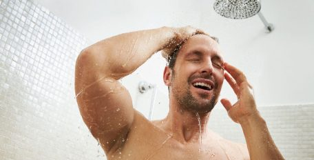 Ein Mann genießt eine warme Dusche. Das Wasser rieselt angenehm von oben herab.