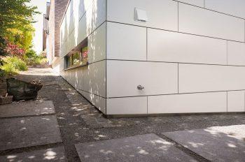 An einer Hausecke schaut fast unmerklich ein Wasserhahn mit Anschluss für den Gartenschlauch aus der Wand.