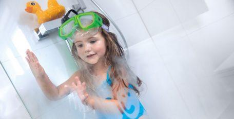 Ein kleines Mädchen, in blauem Badeanzug und mit grüner Taucherbrille, malt an dem beschlagenen Glas in der Dusche.