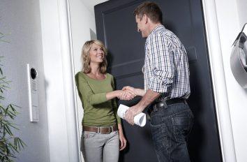 Die Besitzerin eines Eigenheims verabschiedet mit einem Handschlag und Lächeln den Installateur: Die Trinkwasseranlage ist gewartet.