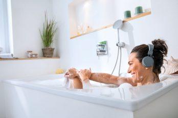 Eine Frau entspannt in der Badewanne und genießt über Kopfhörer Musik.