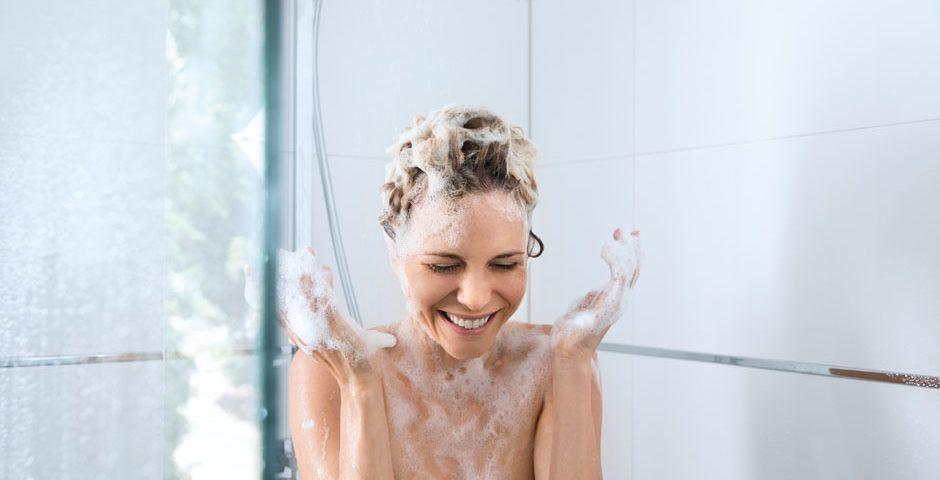 Eine Frau steht mit eingeschäumten Haaren unter der Dusche, aber das Wasser bleibt aus.