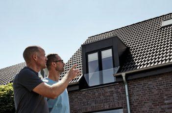 Zwei Männer schauen an einem modernen Wohnhaus empor.