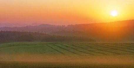 Blick über eine endlos weite Landschaft mit Wiesen und Wäldern, im Hintergrund geht leuchtend die Sonne auf.