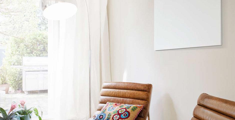 Die Infrarotheizung hängt an der Wand im Wohnzimmer über der gemütlichen Sofaecke.