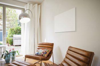 In einem Wohnzimmer scheint ein weißes Bild an der Wand zu hängen. Aber der Schein trügt. Es ist eine Elektroheizung: ein Infrarotheizkörper.