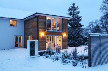 Ein Haus in winterlicher Abenddämmerung. Alles ist schneebedeckt, durch die Fenster scheint stimmungsvolles Licht in den Garten. Dort steht die Außeneinheit einer Wärmepumpe. Diese Elektroheizung versorgt das ganze Haus mit Wärme.