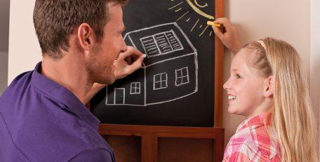 Ein Mann und ein blondes Mädchen zeichnen auf einer Kreidetafel ein Haus mit PV und eine strahlende Sonne.