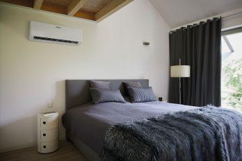 Über einem Doppelbett ist an die Wand das schlanke Innengerät einer Split-Klimaanlage angebracht.