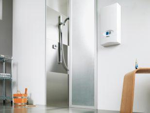 Ein elektronisch gesteuerter Durchlauferhitzer hängt dezent an der Wand außerhalb einer Dusche.