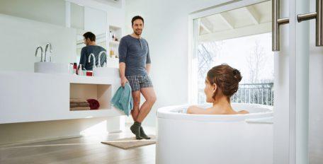Eine Frau genießt ihr Bad, ein Mann lehnt entspannt am Waschtisch – Warmwasser mit der richtigen Temperatur ist selbstverständlich.