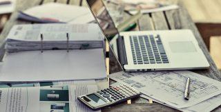 Auf einem Tisch sind Pläne und Unterlagen für die Heizung im Neubau ausgebreitet. Noch bevor der Hausbau startet wird geprüft, mit welcher Heizung die besten Förderungen möglich sind.