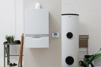 In einer Kellernische steht ein Warmwasserspeicher, daneben hängt ein Gas-Brennwertgerät an der Wand.