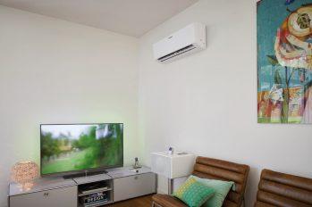 In einem Wohnzimmer läuft ein Fernsehgerät; an der Wand ist eine Klimaanlage montiert.