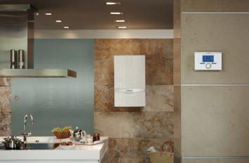 In einer modernen, eleganten Küche hängt im Hintergrund ein Heizgerät an der Wand.