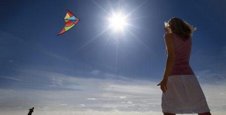 Extreme Hitze in Folge des Klimawandels: Eine Frau steht am Strand in der grellen Sonne und sieht beim Drachensteigen zu.