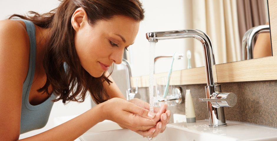 Eine Frau mit langen braunen Haaren schöpft mit beiden Händen an einem Waschtisch Wasser aus einem Wasserhahn