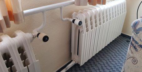 Unter einem Fenster befindet sich eine alte massive Heizung mit zwei Thermostatventilen