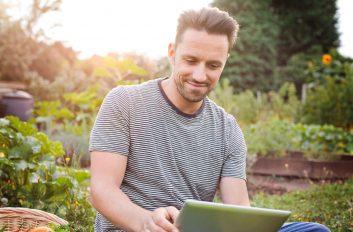 Ein Mann sitzt im Garten und vergleicht die absehbaren Mehrkosten für Energie mit der Investition in eine neue Heizung.