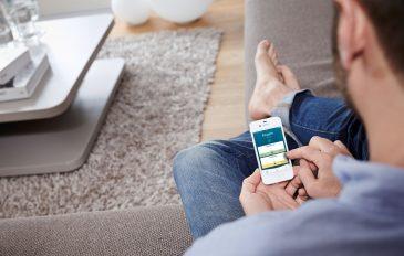 Ein Mann sitzt mit dem Smartphone in der Hand im Wohnzimmer und wählt per App seine Wunschtemperatur aus.