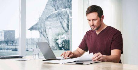 Eine Mann sitzt mit seinem Laptop und vielen Papieren, die er prüfend anschaut, an einem Tisch vor einem Fenster.