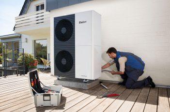 : Ein Fachhandwerker montiert eine Wärmepumpe als Maßnahme eines individuellen Sanierungsfahrplans.