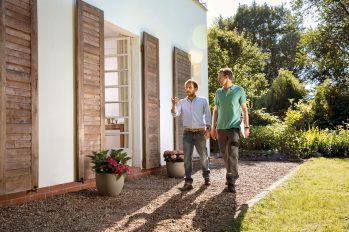 Eigentümer und Energieeffizienz-Experten gehen um das Haus, damit ein individueller Sanierungsfahrplan erstellt werden kann.
