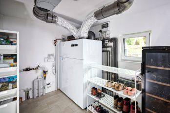 In einem knapp bemessenen Haustechnikraum steht eine moderne Heizungsanlage, in der eine Wärmepumpe mit einer Lüftungsanlage kombiniert ist.