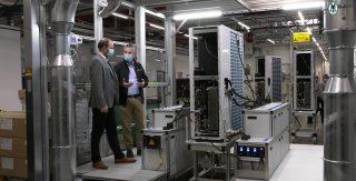 Zwei Männer stehen in einer Fabrikationshalle von Vaillant und schauen sich eine Wärmepumpe made in Remscheid an