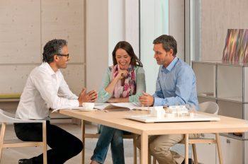 Bauherrenpaar sitzt im Beratungsgespräch mit einem Architekten an einem Tisch. Diskutiert wird, welche Effizienzhaus-Stufe nach BEG wie hoch gefördert wird.