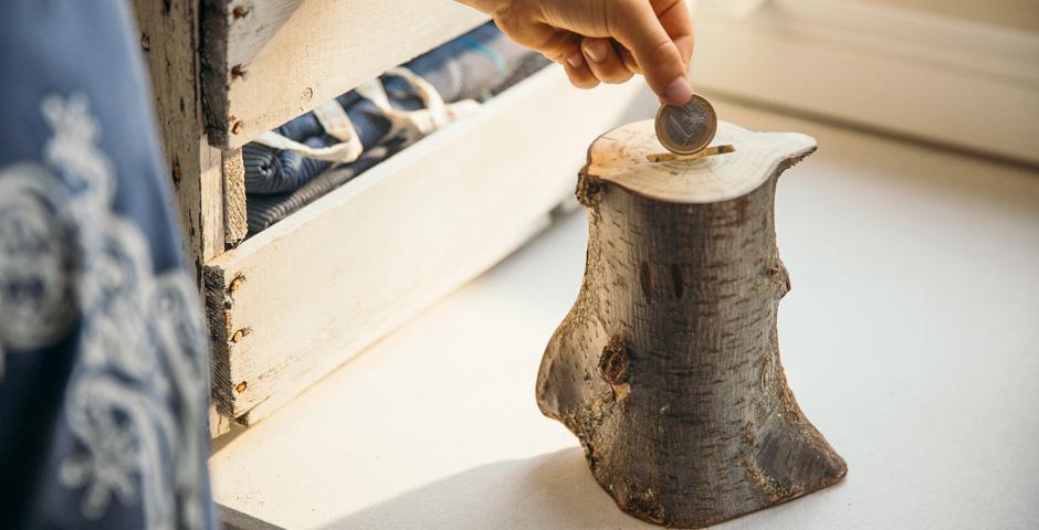 Jemand wirft einen Euro in eine Spardose aus Holz.