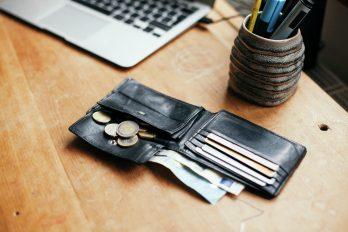 Ein geöffnetes Portemonnaie liegt auf dem Tisch. Münzen, Geldscheine und Kreditkarten schauen heraus.