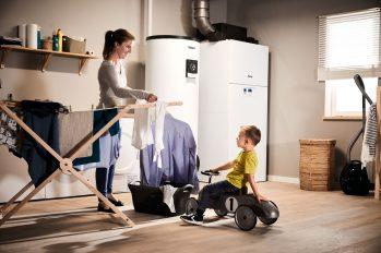 Eine Frau hängt im Hauswirtschaftraum Wäsche auf. Dabei unterhält sie sich mit ihrem kleinen Sohn. Im Hintergrund steht eine moderne Heizungsanlage.