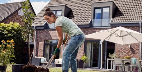 Eine Frau pflanzt im Garten ihres Hauses einen Baum.
