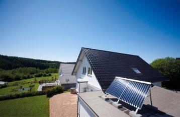 Solarkollektoren sind auf dem Garagendach neben einem Einfamilienhaus aufgeständert.