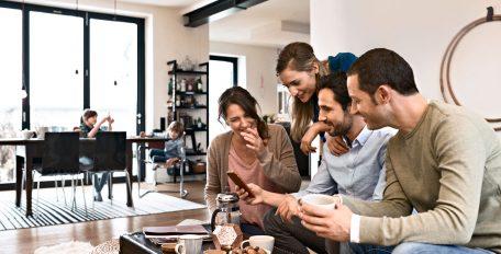 4 fröhliche junge Menschen sitzen in einem offenen Raum an einem Tisch und betrachten etwas auf einem Smartphone.