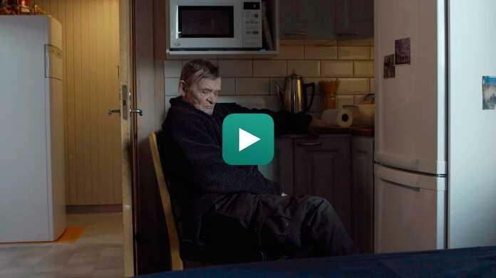 Ake sitzt in siner Küche mit seiner Wärmepumpe im Hintergrund | Vaillant