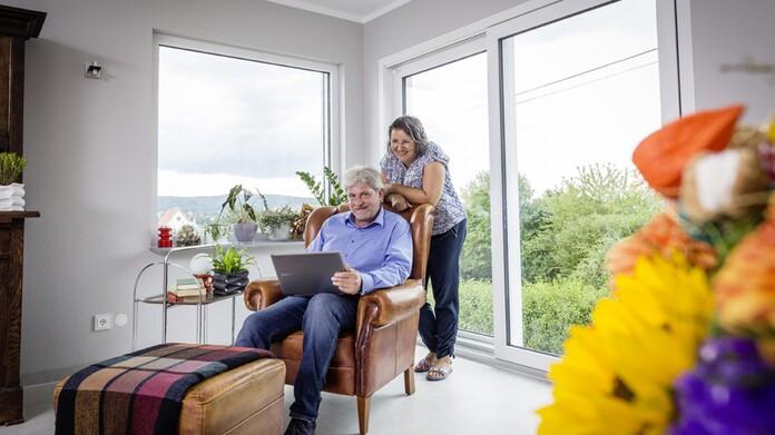 Ehemann Norbert sitzt im Sessel und Egefrau Christine sthet hinter ihm. Beide freuen sich über die neue Luft-/Wasser-Wärmepumpe von Vaillant.