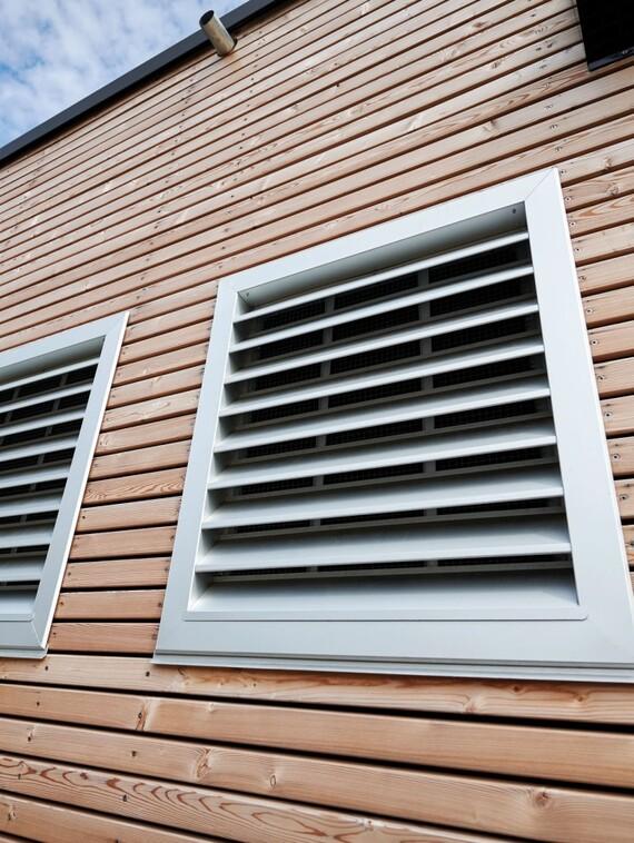 Architektonisch perfekt, auf Wunsch sogar beliebig lackierbar: die Gitter vor den Zu- und Abluftöffnungen für die Wärmepumpe. Darüber der Lufteinlass für die KWL-Anlage.