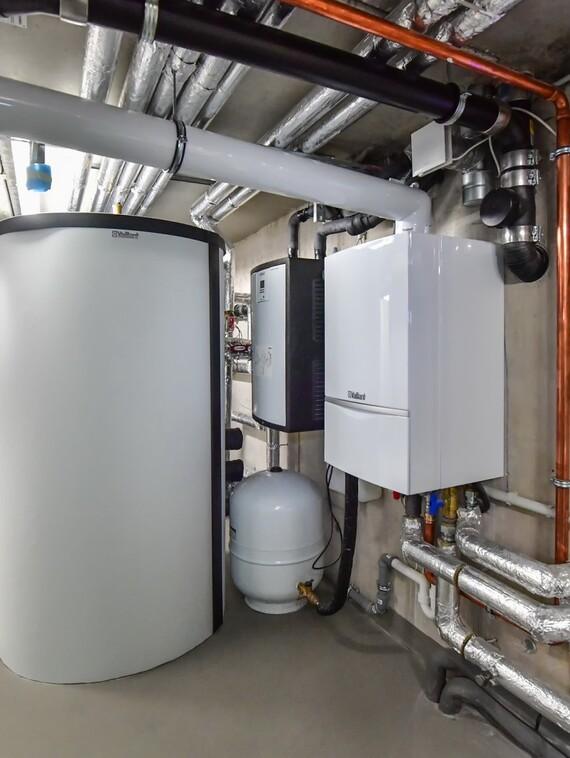 """Blick in den knapp bemessenen, gleichzeitig aber sehr aufgeräumten und übersichtlich ausgestatteten Technikraum des Neubaus. Rechts das wandhängende Gas-Brennwertgerät """"ecoTEC exclusiv"""", in der Mitte einer der beiden 800-Liter-Speicher vom Typ """"allSTOR"""", im Hintergrund die beiden Trinkwasserstationen """"aquaFLOW"""" zur hygienischen Trinkwarmwasserbereitung."""