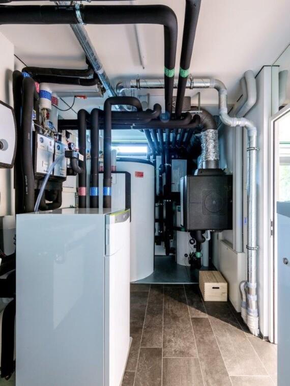 Ein Blick in den Technikraum: rechts im Vordergrund der Batteriespeicher, in der Raummitte die Luft/Wasser-Wärmepumpe, im Hintergrund rechts das Abluftmodul mit Luft/Sole-Wärmetauscher, links der Multifunktionsspeicher mit Trinkwasserstation.